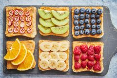 Wholegrain bread slices with peanut butter and various fruits stock photography