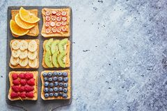 Wholegrain bread slices with peanut butter and various fruits stock photos