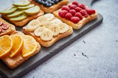 Wholegrain bread slices with peanut butter and various fruits royalty free stock images