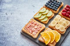 Wholegrain bread slices with peanut butter and various fruits stock image