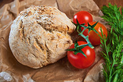 Wholegrain brioches made with coriander seeds. And tomatoes, served on paper and wooden tray; close up Stock Photos