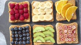 Wholegrain broodplakken met pindakaas en diverse vruchten stock footage