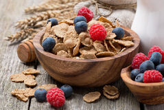Wholegrain flakes with berries and jug of milk on wooden table Stock Photography