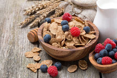 Wholegrain flakes with berries and jug of milk on wooden table Stock Photo