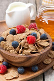 Wholegrain flakes in a bowl with fresh berries, honey and milk Royalty Free Stock Photo