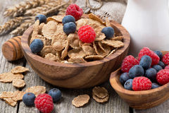 Wholegrain flakes with fresh berries and jug of milk. On wooden table, close-up Stock Images