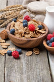 Wholegrain flakes with fresh berries and milk on wooden table Stock Photography