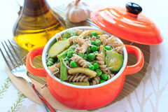 Wholegrain pasta med gröna grönsaker i keramisk panna Royaltyfri Foto
