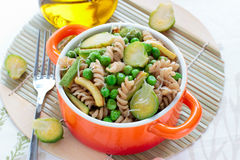 Wholegrain pasta med gröna grönsaker i keramisk panna Arkivbild