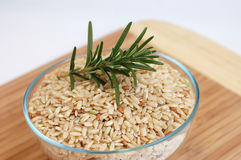 Wholegrain Rice and Fresh Rosemary. A glass bowl full of wholegrain rice and freshly picked rosemary on a wooden cutting desk Stock Photos