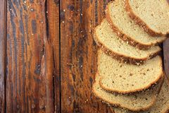 Wholegrain sliced organic bread composed of oats and flax seeds on wooden table. Copy space. Top view stock image