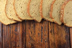 Wholegrain sliced organic bread composed of oats and flax seeds on wooden table. Copy space. Top view stock photos