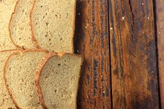 Wholegrain sliced organic bread composed of oats and flax seeds on wooden table. Copy space. Top view royalty free stock image