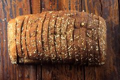 Wholegrain sliced organic bread composed of oats and flax seeds on wooden table. Healthy Diet. Top view stock images