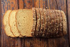 Wholegrain sliced organic bread composed of oats and flax seeds on wooden table. Healthy Diet. Top view stock photography