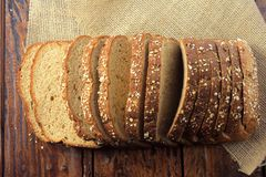 Wholegrain sliced organic bread composed of oats and flax seeds on wooden table. Healthy Diet. Top view stock photo