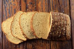 Wholegrain sliced organic bread composed of oats and flax seeds on wooden table. Healthy Diet. Top view stock image