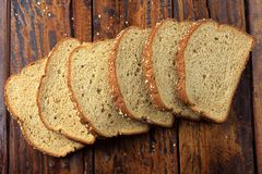 Wholegrain sliced organic bread composed of oats and flax seeds on wooden table. Healthy Diet. Top view royalty free stock images