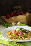 Wholegrain spaghetti pasta with fresh tomato sauce and spring on. Ions on a plate, in the dark background some ingredients such as parmesan cheese, tomatoes and Stock Photos