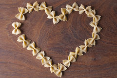 Wholekorn Pasta heart design. Wholegrain farfalle pasta heart design on a wooden background Stock Photography