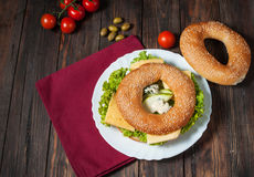Wholemeal bagel with green pesto, fresh vegetables, cheese, tomato and pear Stock Photography