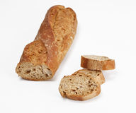 Wholemeal baguette. A half of a wholemeal baguette and three pieces against a white background.Selective focus Stock Images