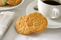 Wholemeal Biscuits. Two brown wholemeal biscuits with a white cup and saucer stock photography
