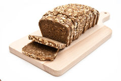 Wholemeal bread. Sliced wholemeal bread on kitchen board isolated on white background Stock Photo