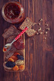 Wholemeal bread with apricot jam surrounded by dry fruit. Vintag Royalty Free Stock Photos