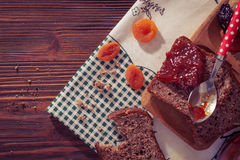 Wholemeal bread with apricot jam surrounded by dry fruit. Stock Images