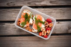 Wholemeal bread with cheese and salmon in a plastic container. Dill and almond with cherry tomatoes. Healthy sandwiches stock photography