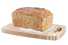 Wholemeal bread on a chopping board Royalty Free Stock Photos