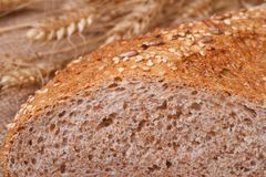 Wholemeal bread with sesame seeds and wheat ears Royalty Free Stock Photography