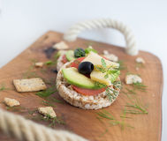 Wholemeal bread snack. With cheese, avocado, olive, tomato and greens Stock Image