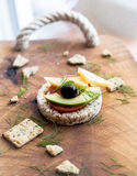 Wholemeal bread snack. With cheese, avocado, olive, tomato and greens Stock Photo