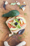 Wholemeal bread snack. With cheese, avocado, olive, tomato and greens Royalty Free Stock Photography