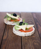 Wholemeal bread snack. With cheese, avocado, olive, tomato and greens Royalty Free Stock Photos