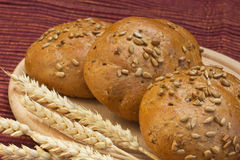 Wholemeal bread with wheat ears on the table. Royalty Free Stock Photography