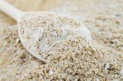 Wholemeal flour macro on wooden spoon. Royalty Free Stock Photo