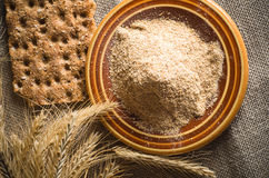 Wholemeal flour and wheat on cloth sack Stock Image