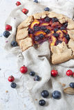 Wholemeal french galette with fruits sliced apricots peaches and blueberries on vintage rustic background with fresh fruits and ro Royalty Free Stock Photo