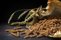 Wholemeal pasta fusilli from spelt in a paper bag and grain ear stock photography