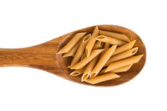 Wholemeal penne pasta on a wooden spoon. A wooden spoon with wholemeal penne pasta. Isolated on white Royalty Free Stock Photos