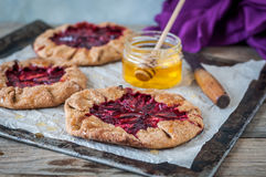 Wholemeal Plum Galettes with Honey. Rustic Wholemeal and Brown Sugar Plum Galettes with Honey Stock Image