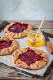 Wholemeal Plum Galettes with Honey. Rustic Wholemeal and Brown Sugar Plum Galettes with Honey, copy space for your text Stock Photos