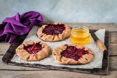 Wholemeal Plum Galettes with Honey. Rustic Wholemeal and Brown Sugar Plum Galettes with Honey, copy space for your text Royalty Free Stock Photos