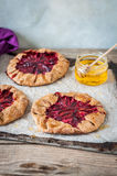 Wholemeal Plum Galettes with Honey. Rustic Wholemeal and Brown Sugar Plum Galettes with Honey, copy space for your text Royalty Free Stock Images