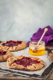 Wholemeal Plum Galettes with Honey. Rustic Wholemeal and Brown Sugar Plum Galettes with Honey, copy space for your text Stock Image