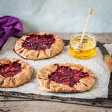 Wholemeal Plum Galettes with Honey. Rustic Wholemeal and Brown Sugar Plum Galettes with Honey, copy space for your text, square Stock Images