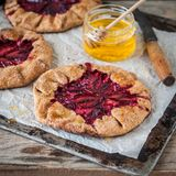 Wholemeal Plum Galettes with Honey. Rustic Wholemeal and Brown Sugar Plum Galettes with Honey, square Stock Photos
